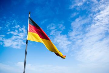 German flag outside with blue skies behind it